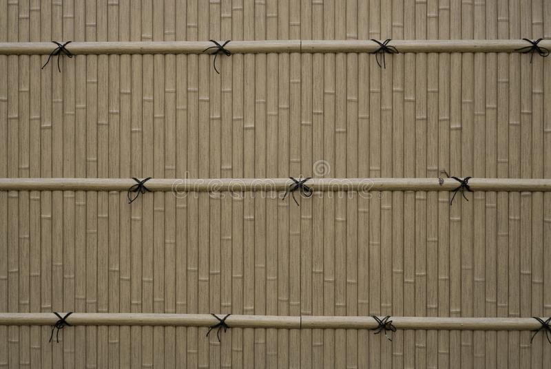 The gray color Bamboo wall and pattern of black rope bind on bamboo twig. Background stock photos