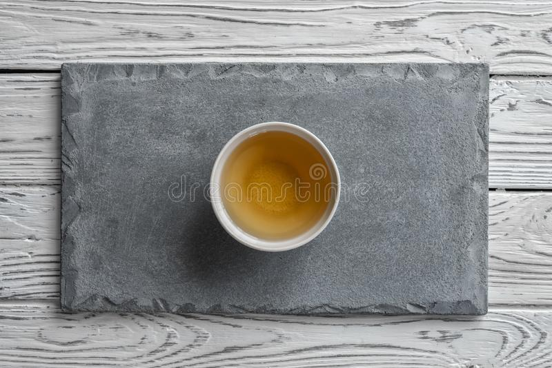 Gray concrete plate on light wooden background and a Cup of tea stock image