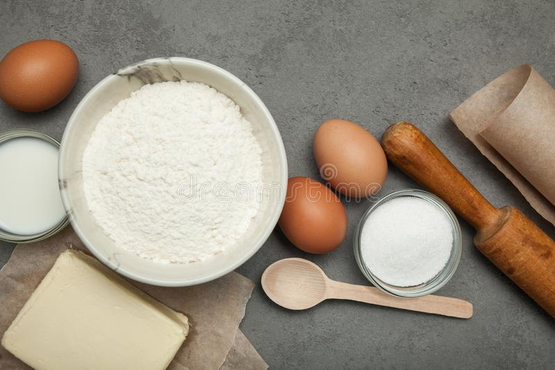 Gray concrete, sugar, eggs, flour and butter on a white background stock photos