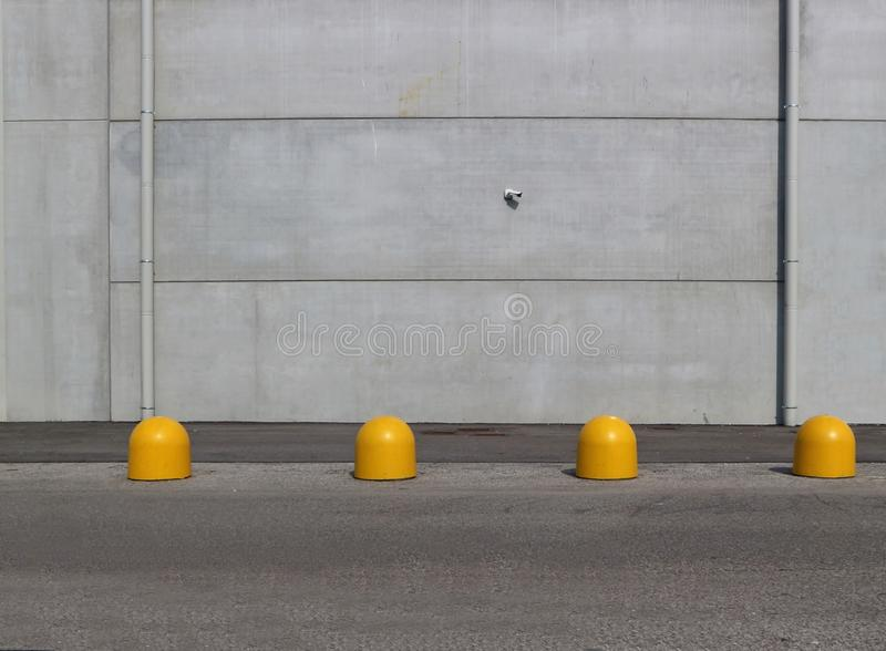 Gray concrete wall with an asphalt road and yellow cement bollards in front. Urban background for copy space royalty free stock photo