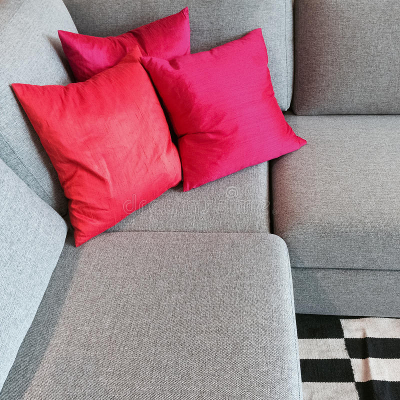 Gray corner sofa with silky red cushions. Comfortable gray corner sofa with silky red cushions stock photography