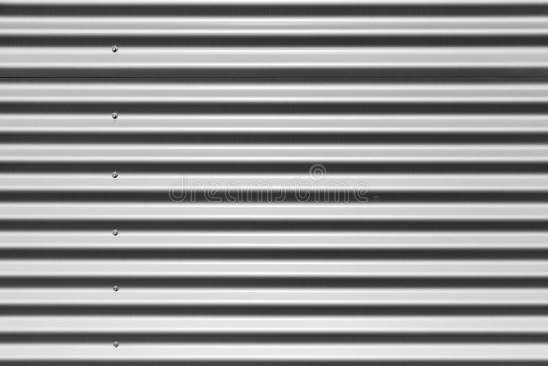 Gray corrugated metal wall texture. Gray corrugated metal wall made of sheets with bolts, industrial wall background photo texture stock photos