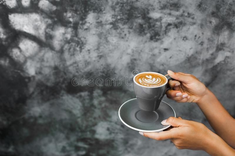 Gray cup of fresh cappuccino in woman hands. On background of gray concrete cement textured wall. Trendy hipster cafe design royalty free stock photography