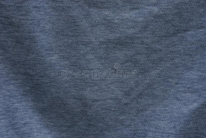 Gray dark texture fabric of crumpled fabric on clothes. Gray dark background of crumpled fabric on clothes stock image