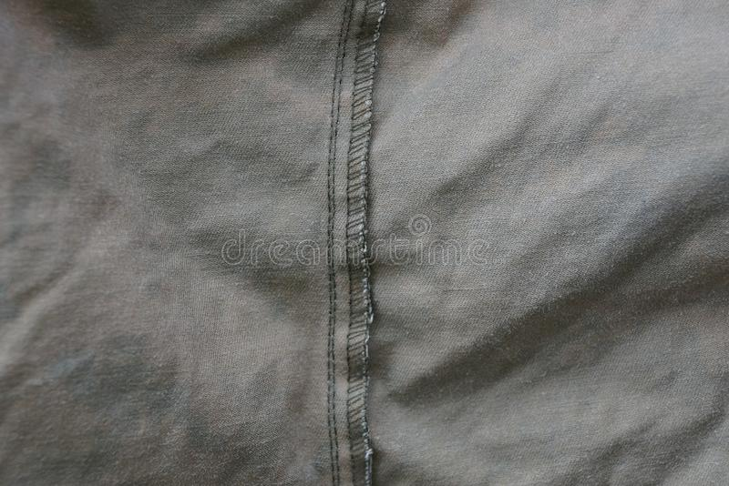 Gray dark texture fabric of crumpled fabric on clothes. Gray dark background of crumpled fabric on clothes stock photography