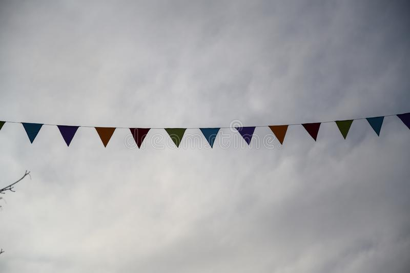Festival garlands in front of a drab gray sky royalty free stock images