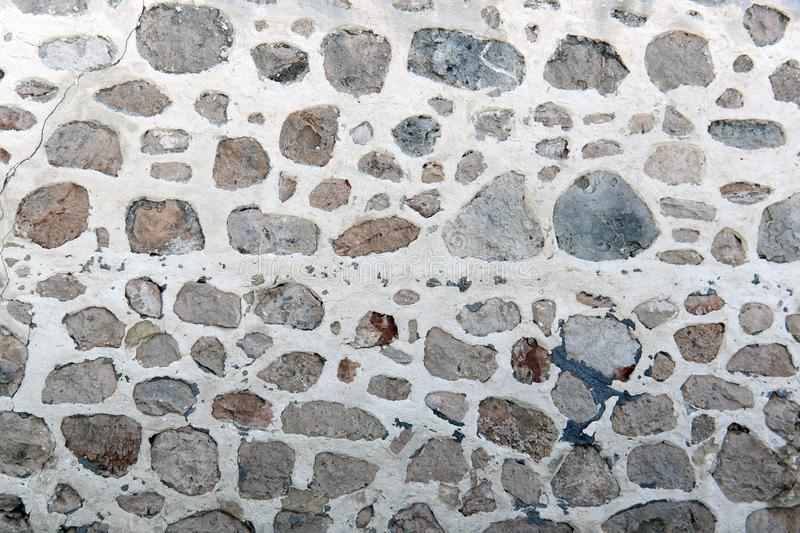 Gray decorative stone wall background. a fragment of a wall with stones and cement. Gray decorative stone wall background. pattern stone surface. a fragment of royalty free stock photos