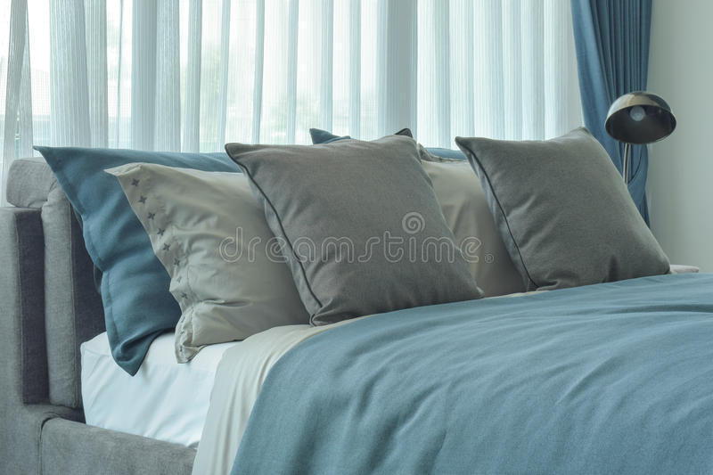 Gray and deep blue pillows setting on bed in deep blue color scheme. Bedding royalty free stock photos