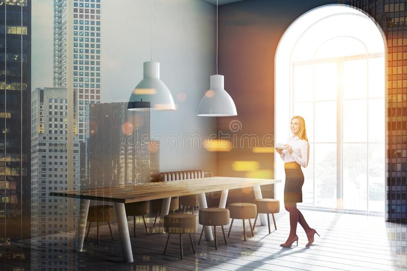 Gray dining room corner, long table, woman royalty free stock photo