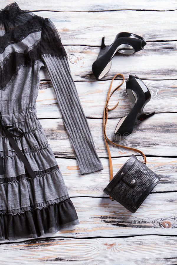 Gray dress and black bag. Luxury heels and classic purse. Lady's dark spring apparel. Goods at extremely low price stock images