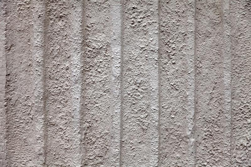 Gray dull background with a rough stone texture with vertical stripes of beige color on the wall of an old antique building. stock images