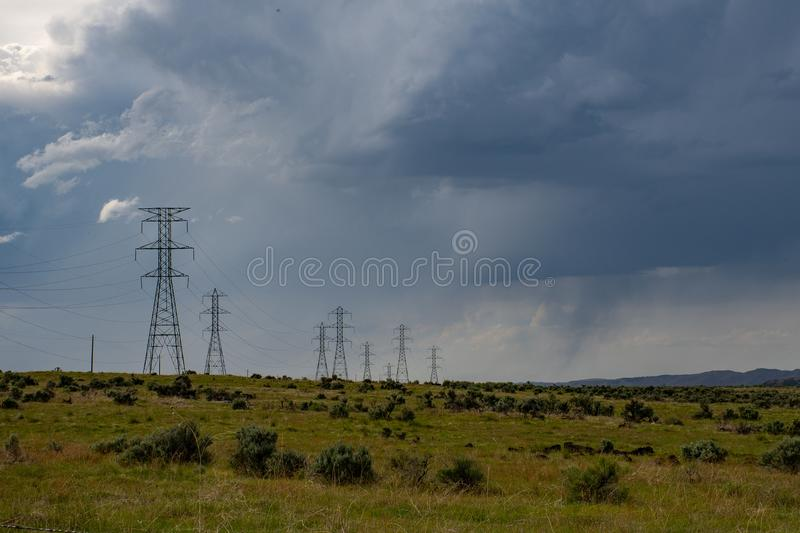 Gray Electric Post on Green Field Under White Clouds and Blue Sky stock image