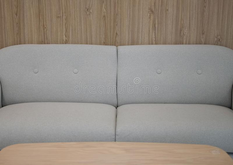Gray fabric sofa couch furniture in living room. Near wood wall stock photography