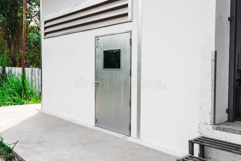 Gray Factory Door argenté sur le mur blanc photo stock