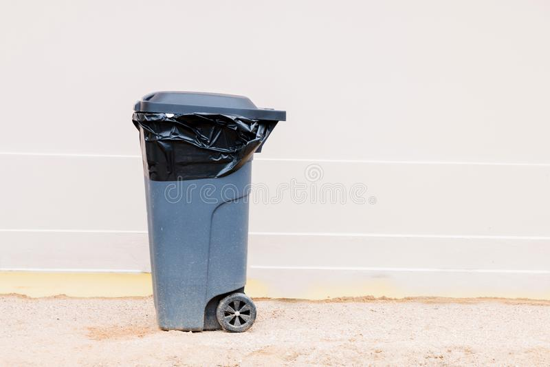 Gray garbage container with garbage bag  on light background, trash can stock images
