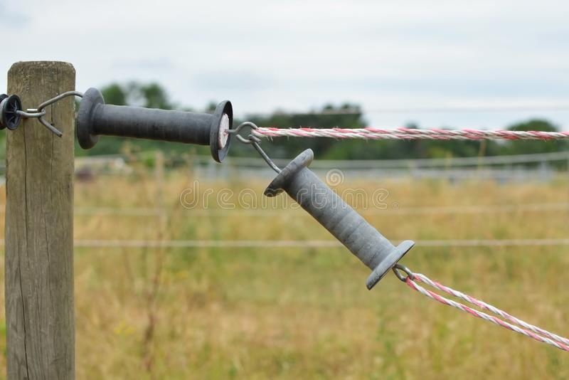 Gray gate handles of closed electric fence around animal paddock stock image
