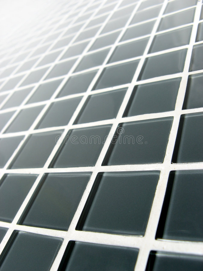 Gray Glass Grid. Gray glass tiled surface at a dynamic angle royalty free stock image