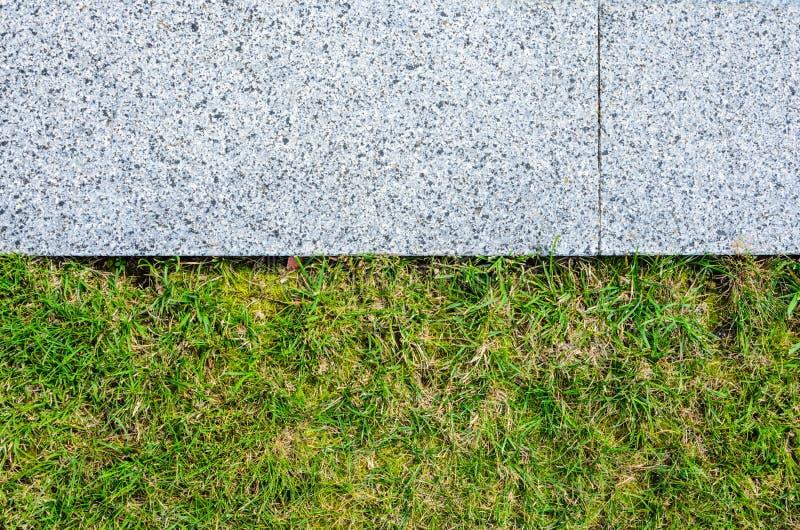 Gray Granite Pavement och gräsgräsmattatextur royaltyfri fotografi