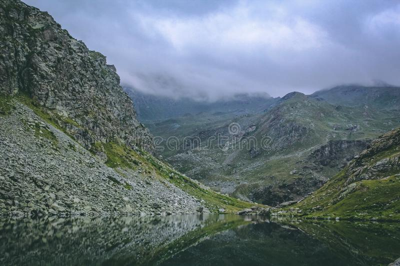Gray and Green Mountains With Body of Water Under Cloudy Sky royalty free stock images
