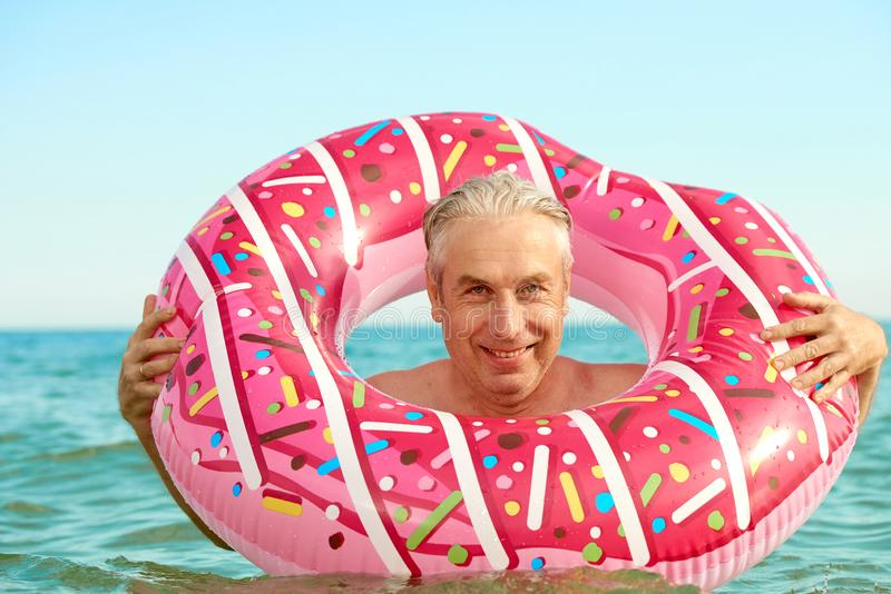 Gray-haired man swims on an inflatable circle in the sea. Gray-haired funny man swims on an inflatable circle in the sea stock image