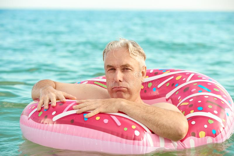 Gray-haired man swims on an inflatable circle in the sea. Gray-haired funny man swims on an inflatable circle in the sea stock photos