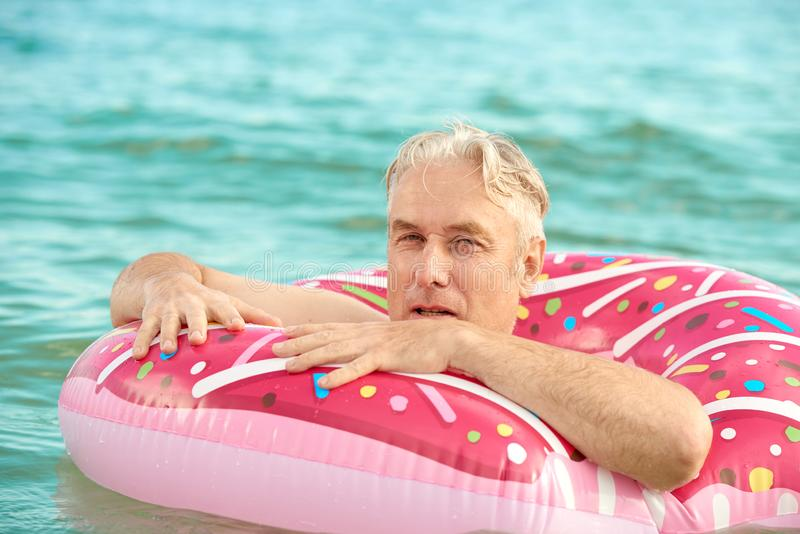 Gray-haired man swims on an inflatable circle in the sea. Gray-haired funny man swims on an inflatable circle in the sea stock photography