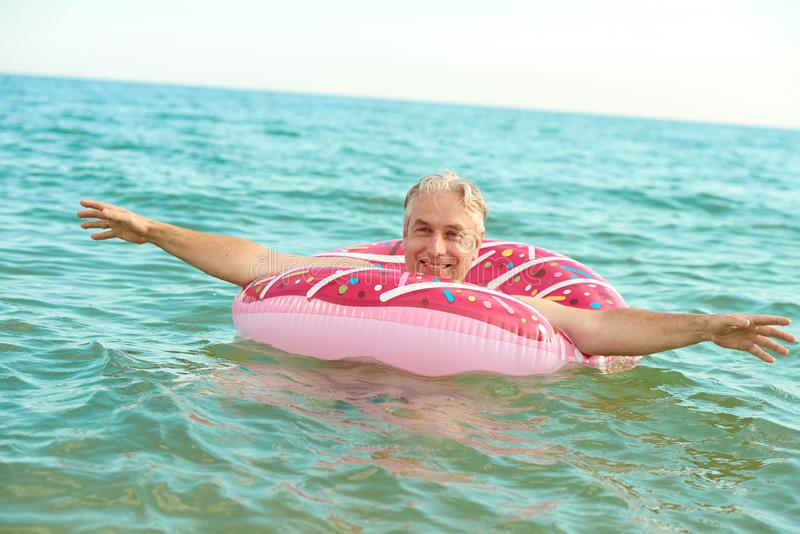 Gray-haired man swims on an inflatable circle in the sea. Gray-haired funny man swims on an inflatable circle in the sea stock photo