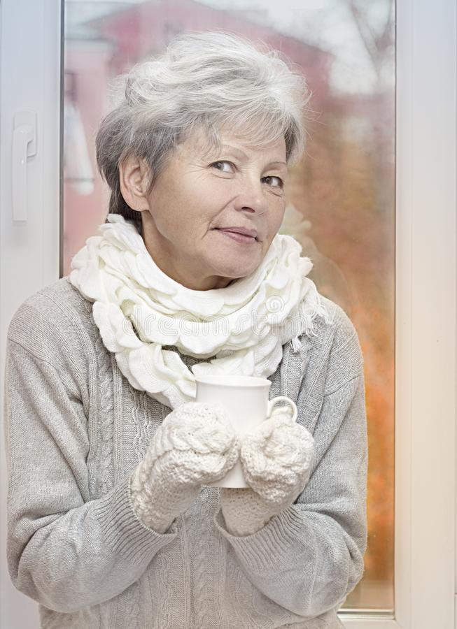 Gray haired woman in white knitted gauntlets drink beverage and smiling on autumn window background. Elderly woman with stock photography