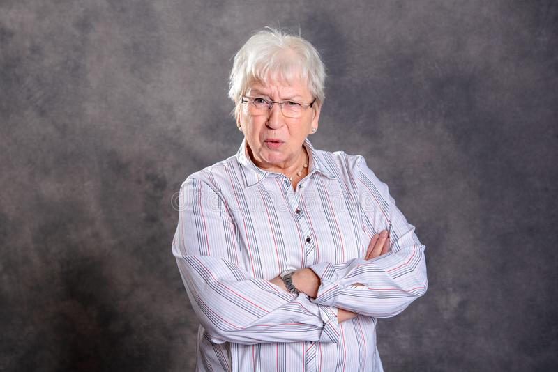 Gray hairy elderly woman with crossed arms looking angry. In front of gray background royalty free stock photo