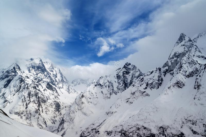 Gray high mountain peaks covered with ice. And beautiful blue sky with clouds at winter day after snow storm. Caucasus Mountains, region Dombay royalty free stock images