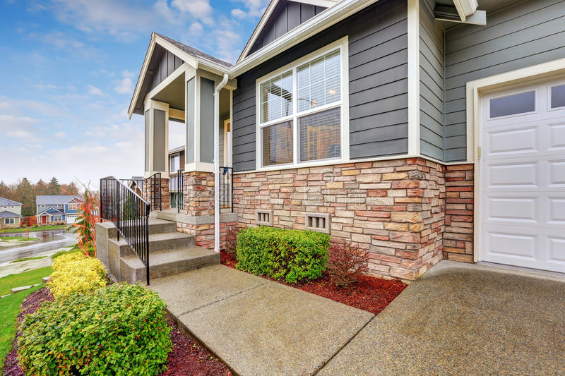 Gray house exterior with column porch. And stone wall trim on a rainy day. Northwest, USA stock image