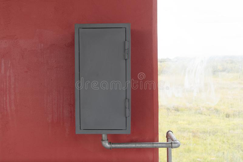 A gray iron box hangs on a red wall, next to a window. Fire box or gas box, a water or gas pipe is connected stock photos