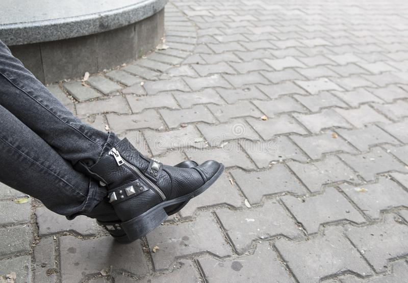 Gray jeans and black boots. With rivets and a zipper lock. Paving slabs. The outside royalty free stock photo