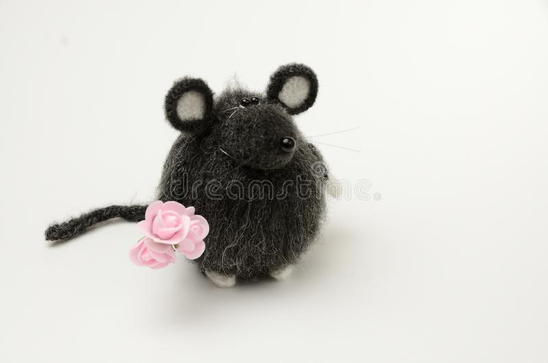 Gray, knitted rat toy with a bouquet of flowers on a white background. Symbol of 2020. On white background stock photo