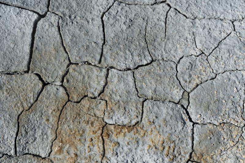 Gray light blue dry cracked surface of volcanic earth stock images