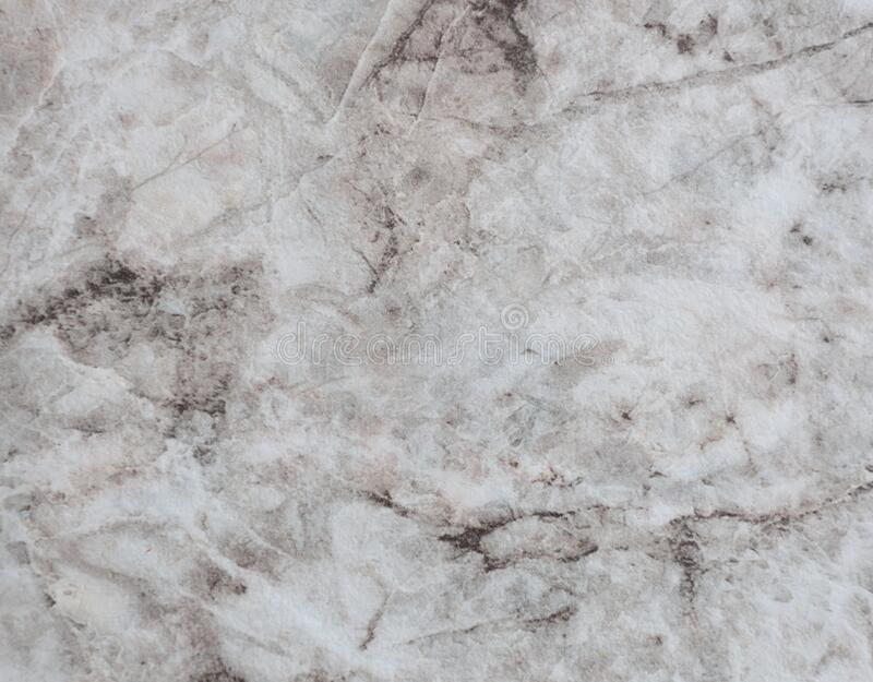 Gray marble, natural stone texture with streaks of brown and yellow color close-up. Background stock photos