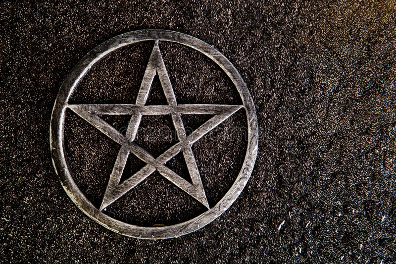 Gray metal pentagram on slate background with water drops stock photo