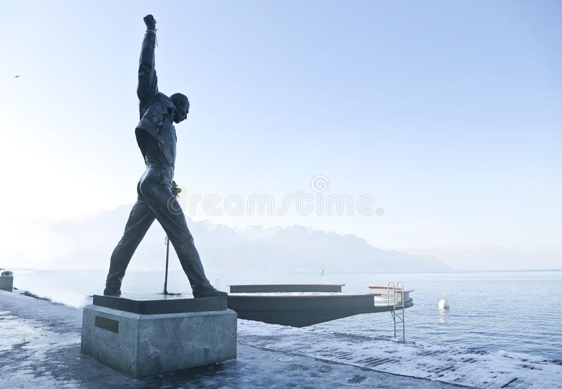 Gray Metal Statue of Man Raising Hand Near Dock royalty free stock photography