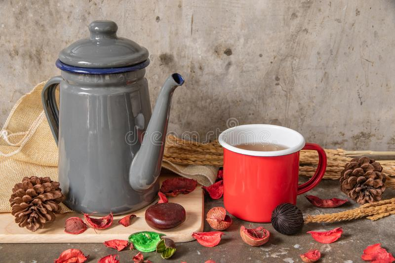 Gray metal teapot and red tin cup on cement table background stock image