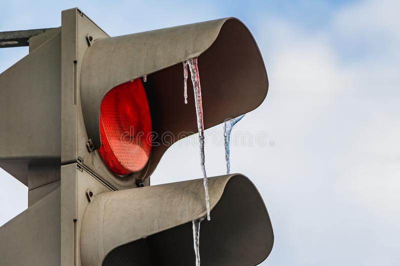 A gray metallic diod traffic light with LED red light on and a group of transparent colored icicles on the blue sky background royalty free stock photos