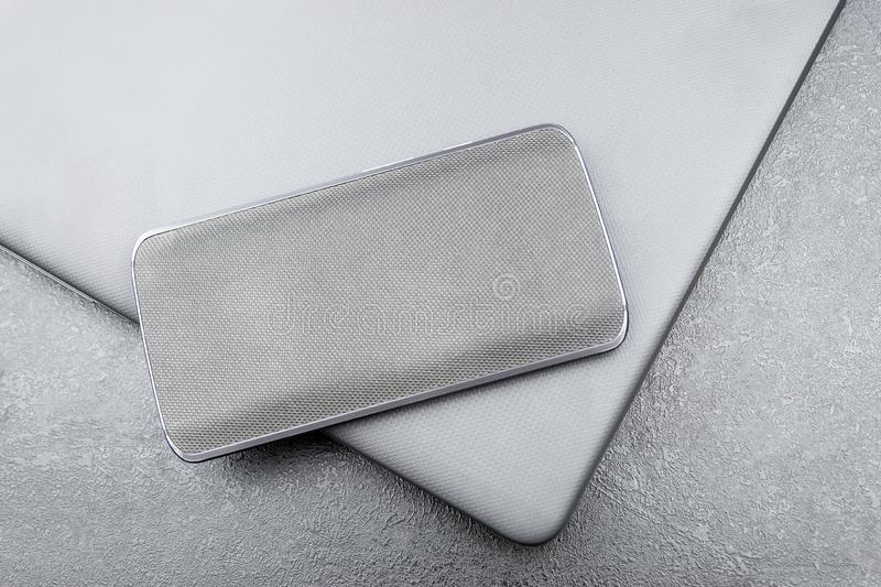 Gray mobile phone with a knitted nylon back lies on a closed textured laptop cover on a gray textural background.  royalty free stock image