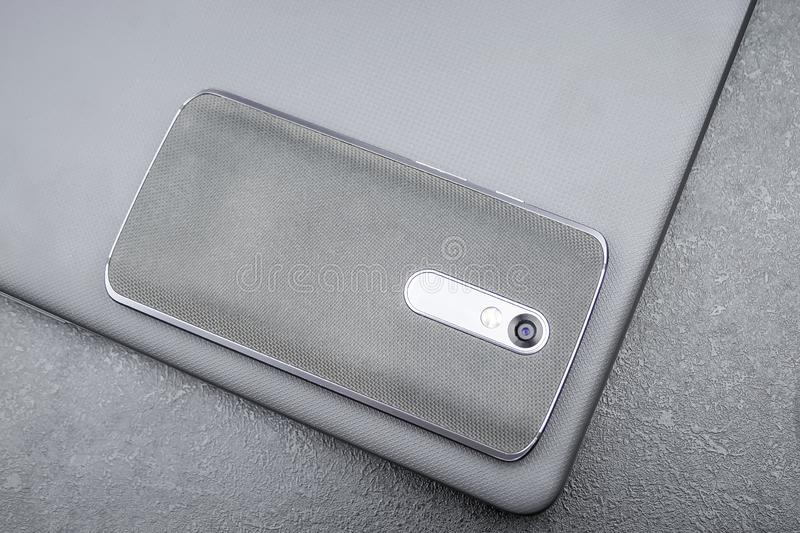 Gray mobile phone with a knitted nylon back lies on a closed textured laptop cover on a gray textural background.  royalty free stock photos