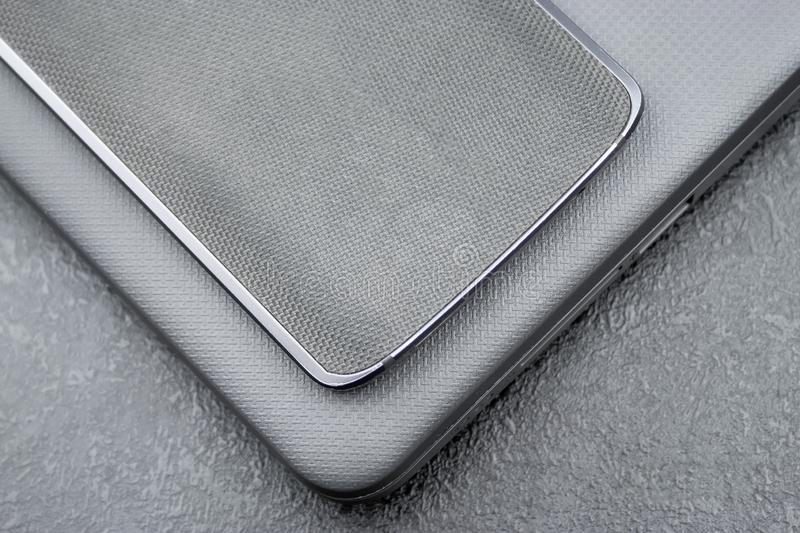 Gray mobile phone with a knitted nylon back lies on a closed textured laptop cover on a gray textural background.  royalty free stock images