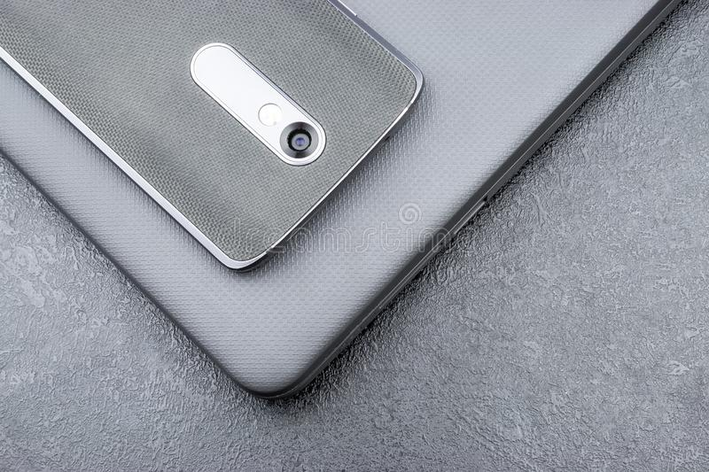 Gray mobile phone with a knitted nylon back lies on a closed textured laptop cover on a gray textural background.  stock photos