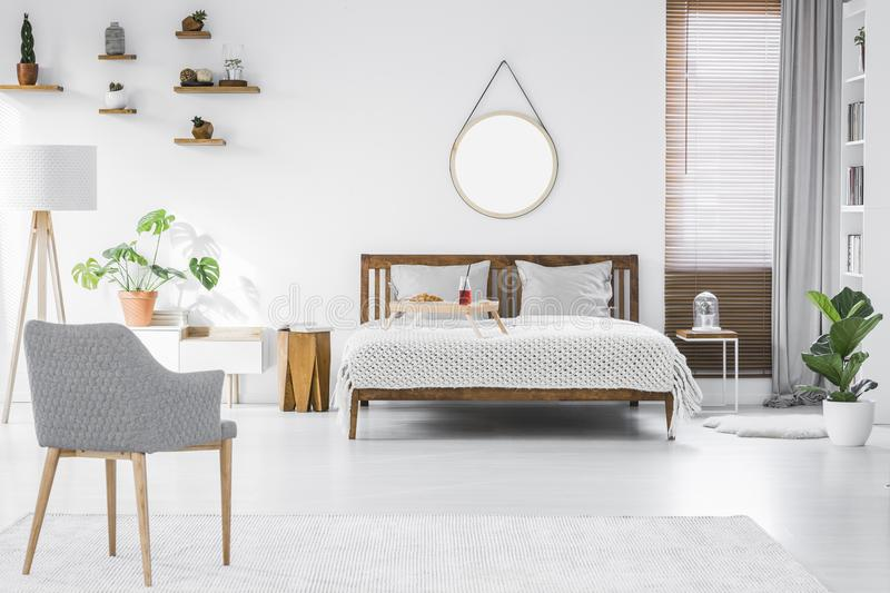 Gray, modern armchair, breakfast tray on a double bed and wooden stock photos