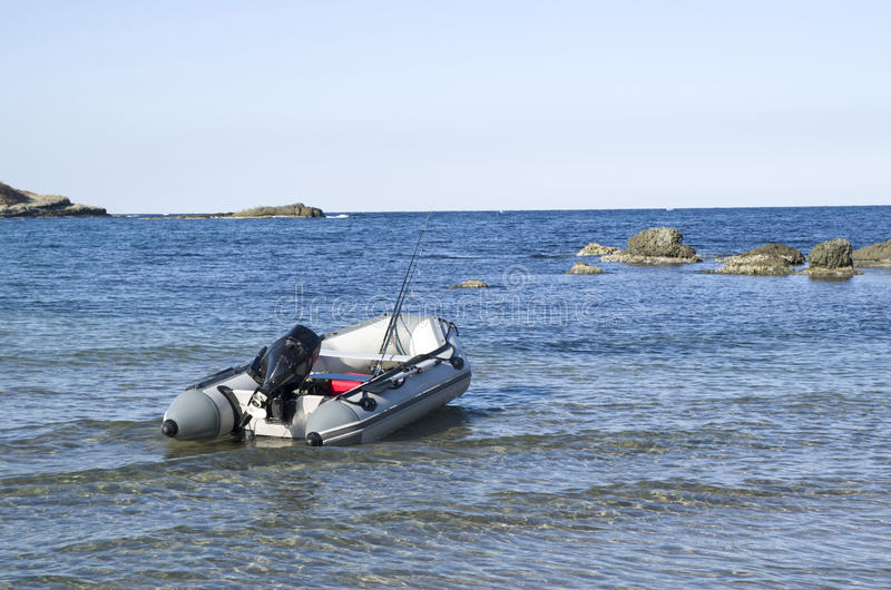 Gray motor rubber inflatable boat in bay. Gray motor rubber inflatable boat with fishing tackles in bay stock photography