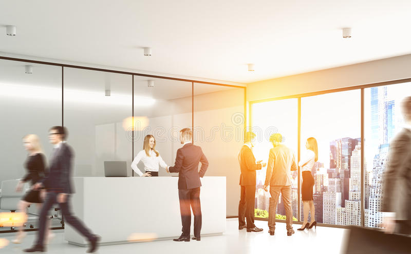 Gray office with people. Businesspeople are passing by a reception counter in an office with gray walls. 3d rendering, toned image royalty free stock photo