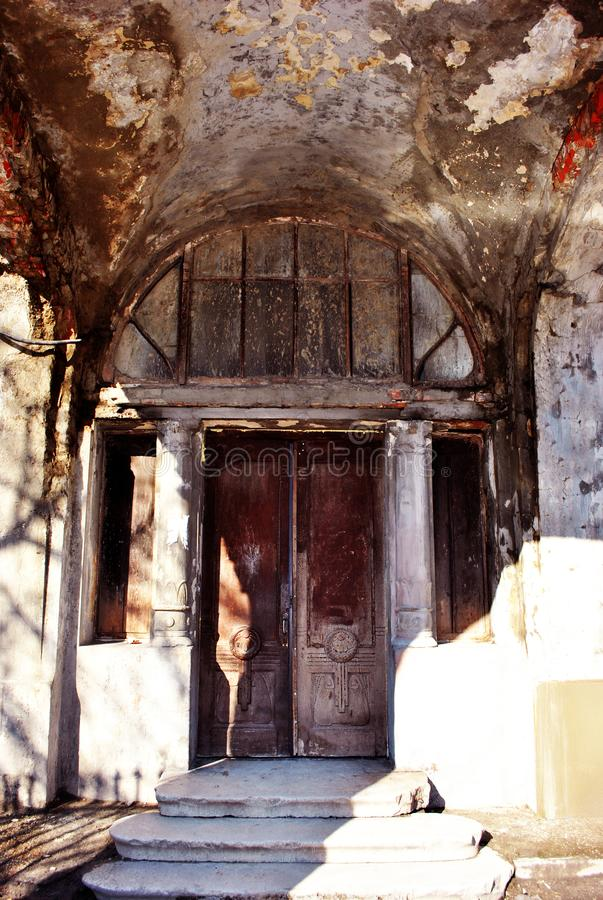 Gray old castle ruined walls and door with columns on sides, steps with bright sunlight. Kharkiv, Ukraine royalty free stock photo