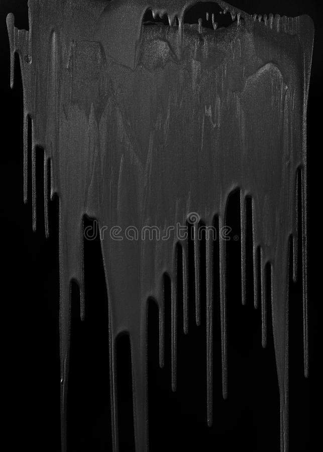 Gray paint dripping isolated. On black background royalty free stock image