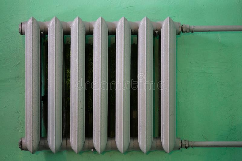 Gray painted cast iron water radiator on green wall royalty free stock images